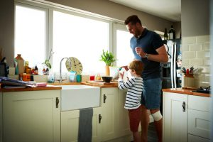 Little boy helping his father to make breakfast in kitchen